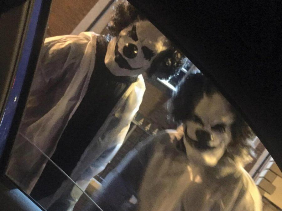 Two clowns allegedly carrying weapons stand outside of a car window.