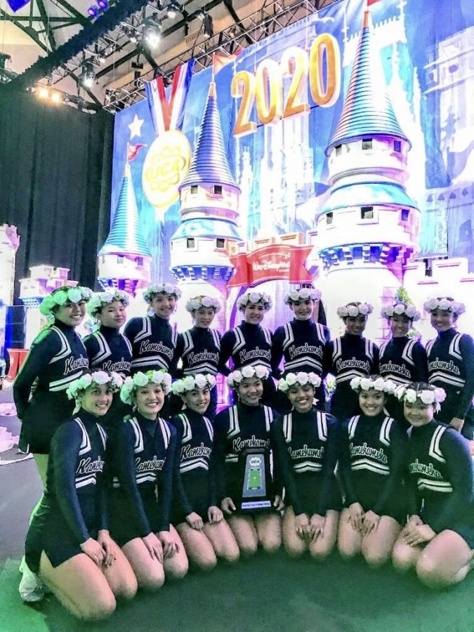 Here, is the varsity cheerleading team with their trophy in front of the finals competition castle.