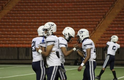 Teammates share a moment together before facing Punahou in their first game